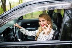 Attraktives Mädchen sitzt in einem modernen Auto Sie schaut durch Fenster und zeigt okayzeichen Stockfoto