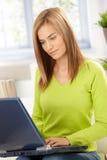 Attraktives Mädchendurchstöberninternet zu Hause im Grün Stockbilder