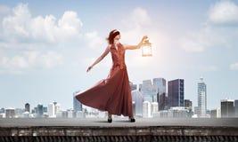 Attraktives Mädchenmuse mit alter Laterne in der Hand am Sommertag Gemischte Medien lizenzfreies stockfoto