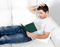 Attraktives Mannlesebuch oder Studieren auf Couch Stockfotografie