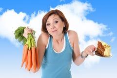 Attraktives Mädchen, das draußen Apfel und süßen Kuchen in der Diät und in der gesunden Nahrung hält Lizenzfreies Stockfoto