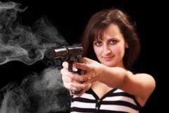 Attraktives Mädchen, das mit Gewehr mit Rauche zielt Stockfotos