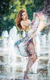 Attraktives Mädchen im mehrfarbigen kurzen Kleid, das mit Wasser an einem heißesten Tag des Sommers spielt Mädchen mit nassem Kle Stockbilder