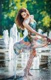Attraktives Mädchen im mehrfarbigen kurzen Kleid, das mit Wasser an einem heißesten Tag des Sommers spielt Mädchen mit nassem Kle Stockfotografie