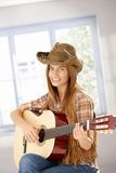 Attraktives Mädchen, welches das Gitarrenlächeln spielt Stockfoto