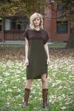 Attraktives Modekleiderblondes M?dchen, das in fallenden Artumgebungen des Herbstlaubs aufwirft stockfoto