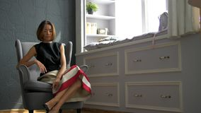 Attraktives Modell sitzt auf einem Sessel, strafft sich die Haare und Posen für den Fotografen für das Cover eines Modemagazins stock footage