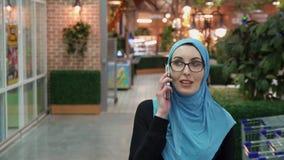 Attraktives moslemisches Mädchen, das auf dem Telefon und dem Lächeln spricht stock footage
