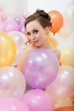 Attraktives nacktes Mädchen, das mit bunten Ballonen aufwirft Stockfotografie