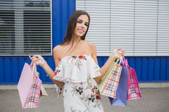 Attraktives, nettes und lächelndes Mädchen herein mit bunten Einkaufstaschen in ihren Händen Untersuchung den Abstand stockfotografie