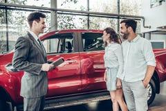 Attraktives Paar spricht mit AutoVerkaufsleiter im Luxusauto-vertragshändler und betrachtet schönes rotes Automobil stockfotografie