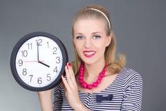 Attraktives Pinupmädchen in gestreiftem Kleid mit Uhr Stockfotos
