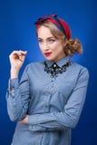Attraktives Pinupmädchenporträt auf blauem Hintergrund Stockfotos