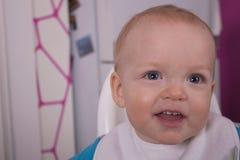 Attraktives Säuglingskind mit Löffel in seinem Mund Stockfotografie