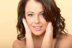 Attraktives schönes junge Frauen-Porträt, das betrachtet und lächelt Stockbilder