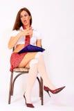 Attraktives Schulmädchen, das auf dem Stuhl sitzt Stockfotografie