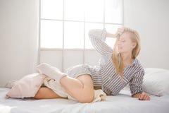 Attraktives spielerisches weibliches Lügen und Berühren ihres blonden Haares Stockbilder