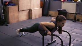 Attraktives sportives Brunettemädchen, welches das Handeln drückt, ups mit Liegestützstangen an der Turnhalle Arbeiten an starken stock video