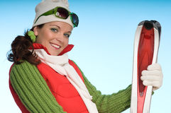 Attraktives sportives Mädchen, das rote Skis anhält Stockbilder