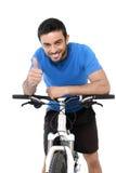 Attraktives Sportmannreitmountainbiketraining, das Daumen aufgibt Stockfotos