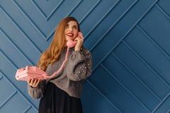 Attraktives stilvolles junges Mädchen mit Retro- rosa Telefon auf Aquahintergrundgefühlen stockfoto