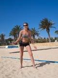 Attraktives Strandmädchen auf dem Strandvolleyballfeld Stockbild