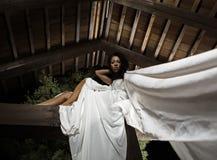 Attraktives suntanned Mädchen in den weißen Kleidhaltungen. Lizenzfreie Stockbilder