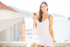 Attraktives trinkendes alkoholisches Cocktail der Frucht der jungen Frau und Genießen ihrer Sommerferien Halten des Glases des ka stockbilder