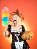 Attraktives vorbildliches Mädchen im Halloween-Haushälterinkostüm Kürbishauptsteckfassungslaterne Geschnitzter Kürbis - lustiges  lizenzfreie stockfotografie