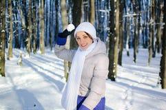 Attraktives weibliches Modell hat Spaß im sonnigen schneebedeckten Park, der im Schneekampf spielt und die Kamera betrachtet lizenzfreies stockfoto
