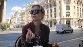 Attraktives weibliches Pariser, ein H?rnchen in einem Stra?encaf? in der Mitte von Paris essend Vor dem hintergrund a stock footage