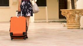 Attraktives weibliches Rollen drehte den Koffer und verließ Hotel, Sommerferien stock footage