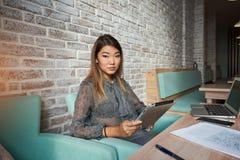 Attraktives weibliches Sitzen mit tragbarem Netzbuch in der Kaffeestube Lizenzfreie Stockfotografie