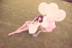 Attraktives weibliches Träumen mit Ballonen stockbild