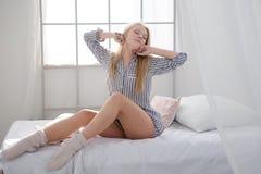 Attraktives zartes weibliches Sitzen auf weißem Bett und dem Ausdehnen Stockfotografie