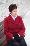Attraktivt äldre kvinnasammanträde på bänk på den snöig gatan för vinter Fotografering för Bildbyråer