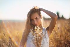 Attraktivt anseende för ung kvinna i ängen som räcker hennes långa hår arkivfoto