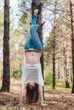 Attraktivt anseende för ung kvinna på händer i en skog utomhus royaltyfri fotografi
