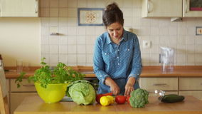 Attraktivt anseende för ung kvinna på köksbord- och klippgrönsaker Den sunda livsstilen, organiska foods, strikt vegetarian, bant lager videofilmer