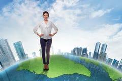 Attraktivt asiatiskt anseende för affärskvinna på stor jord med skysc Arkivbild