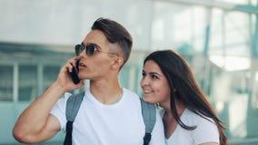 Attraktivt barnparanseende nära flygplatsen En man kallar en taxi eller kallar hemsändningen Kommunikation arkivfilmer