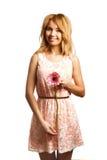 Attraktivt blont kvinnainnehav en blomma royaltyfria foton
