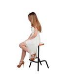 Attraktivt blont kvinnasammanträde på en stol royaltyfri fotografi