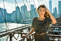 Attraktivt blont kvinnligt modellanseende på den Brooklyn bron med stadssikt på bakgrunden arkivfoton