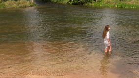 Attraktivt Caucasian tonårigt flickaanseende i floden med Gray Dress lager videofilmer