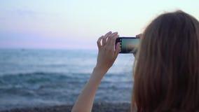 Attraktivt danandefoto för ung kvinna på smartphonen vid havskusten stock video