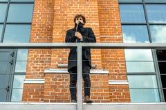 Attraktivt eftertänksamt mananseende på trappuppgång på röd bricked byggande bakgrund fotografering för bildbyråer