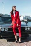 Attraktivt flickaanseende bredvid en retro sportbil på solen Dana kvinnan i en röd dräkt och solglasögon som väntar nära den klas Royaltyfri Fotografi