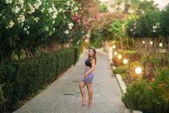 Attraktivt flickaleende i sommartid Solnedg?ng Near blomstra tr?d f?r kvinna royaltyfri bild