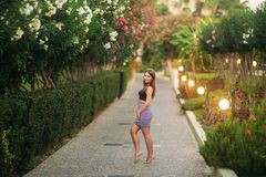 Attraktivt flickaleende i sommartid Solnedg?ng Near blomstra tr?d f?r kvinna arkivfoto